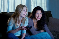 ´Young women watching television, using remote control, smiling´