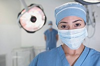 Hispanic female doctor wearing surgical mask in operating room