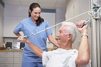 Senior male patient performing physical therapy with nurse