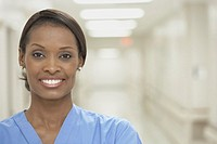 African female nurse smiling in hospital corridor
