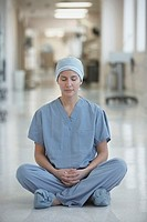 Hispanic female doctor meditating on floor in hospital corridor