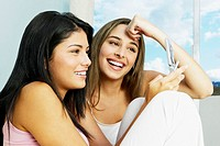Two young Hispanic women looking at cell phone (thumbnail)
