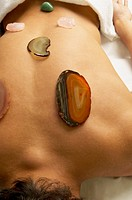 Man receiving stone and crystal spa treatment on back