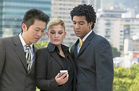 Three businesspeople looking at cell phone