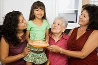 Multi-generational Hispanic female family members smiling in kitchen