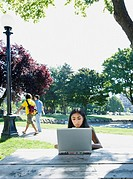 Indian woman typing on laptop outdoors