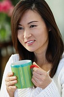 Asian woman holding coffee mug