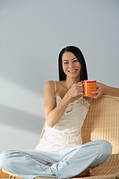 Asian woman holding coffee cup