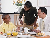 African woman serving breakfast to husband and son
