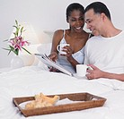 Middle-aged African couple having breakfast in bed