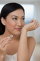 Asian woman smelling perfume on wrist