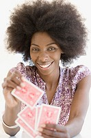 African woman holding playing cards