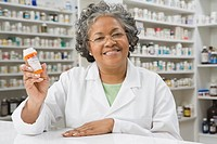 African female pharmacist holding medication