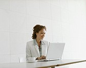 Businesswoman working at laptop with coffee cup