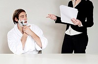 Businessman shaving his face while talking to his colleague