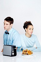 Couple sitting together with toaster and waffles on the table
