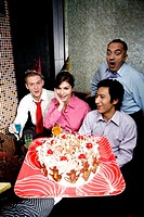 Business people throwing a surprise birthday party for their female colleague