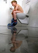 Boy sitting at the toilet desperately