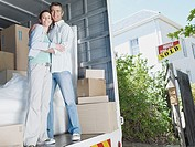 Man and woman standing in moving van smiling with sold sign on house