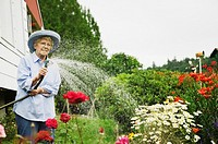 Senior woman watering plants with hose