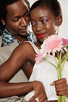 African couple hugging and holding daisies