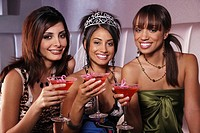 Multi-ethnic women drinking at bachelorette party