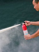 Asian man using fire extinguisher