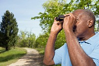Senior African man using binoculars in park
