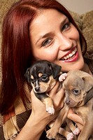 Hispanic woman hugging puppies
