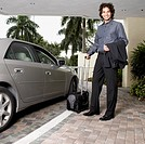 Hispanic businessman holding suitcase next to car