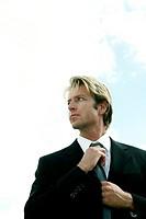 Businessman adjusting his tie while looking away