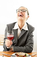 Businesswoman laughing while holding a glass of wine