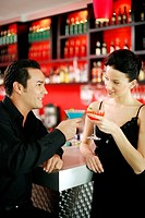 Couple holding drinks while hanging out in a bar