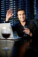 Man waving his hand while holding a glass of wine