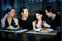 Men and women chatting while having dinner in a restaurant