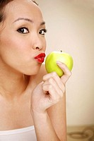 Young woman kissing a green apple