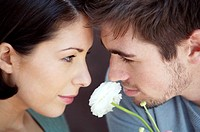 Couple looking at each other with a white rose in between