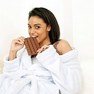 Lady in bathrobe enjoying a bar of chocolate
