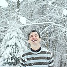 Man looking up smiling with snow dropping on his face