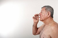 Bare chested senior man drinking water