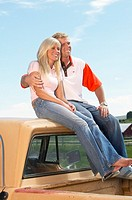 Couple sitting on pick-up truck