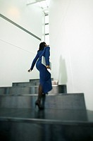 African businesswoman carrying laptop up staircase