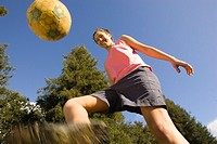 Young woman kicking a soccer ball