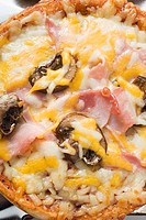Mini-pizza with ham, mushrooms and cheese
