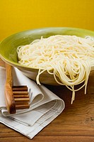 A dish of cooked spaghetti with spaghetti server