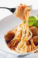 Spaghetti on fork with meatballs and tomato sauce