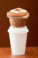 A muffin on a plastic coffee cup