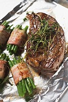 Grilled beef steak with bacon-wrapped beans