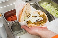 Hand holding opened döner kebab with onions