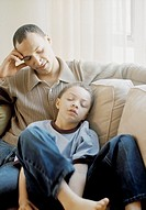 African father and son sitting on sofa